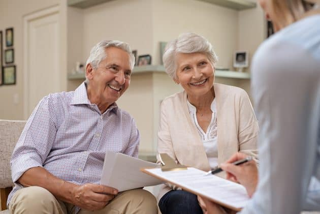 A senior couple works together with a non-profit senior living community representative.