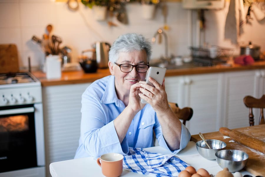 An older woman safely video chatting with loved ones before she begins to cook.