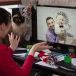 An older woman on a video call with her son and grandson during the holidays.