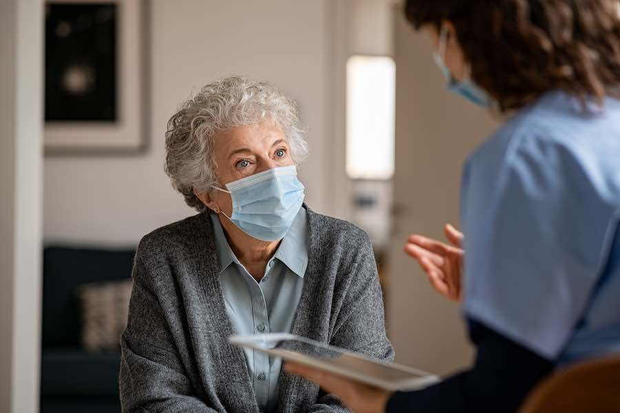 A senior woman talking with a healthcare professional about how she can protect herself from the flu.