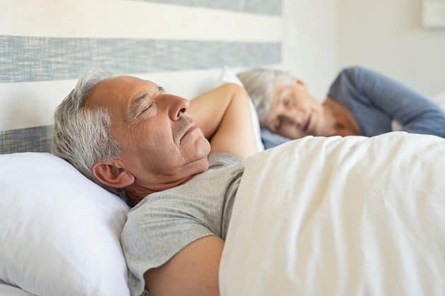 A senior man and woman sleeping in their bed in the morning.