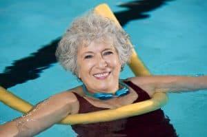 Active older woman enjoys pool exercises for seniors.