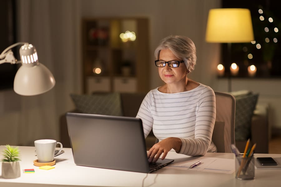 A senior citizen woman participating in an online volunteer opportunity from her own home.