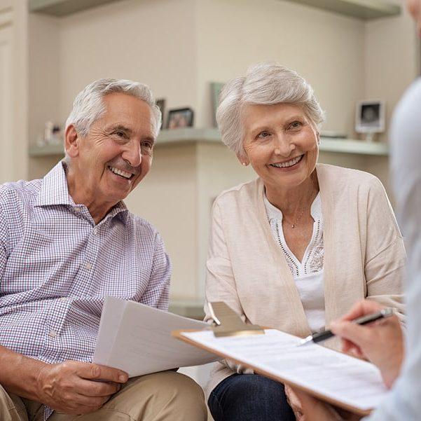A senior couple works together with a non-profit senior living community representative.