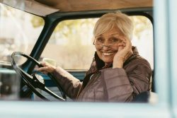 An older adult behind the wheel of her car.