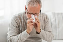 An older man who is blowing his nose due to suffering from the flu.