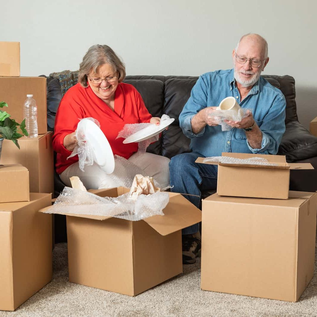 Senior couple packing up their belongings to relocate to a senior living community.
