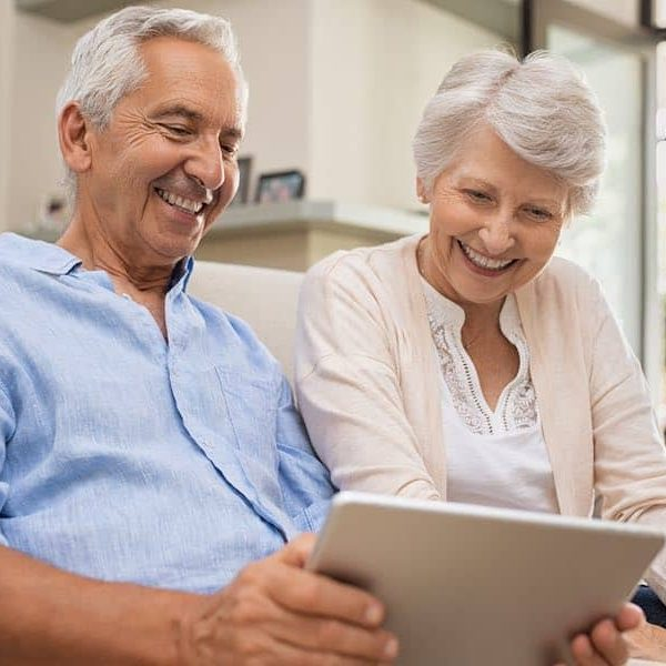 An older adult couple video chatting with friends to stay connected during social distancing.