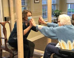Senior resident and family member reaching out to plexiglass divider during a visit