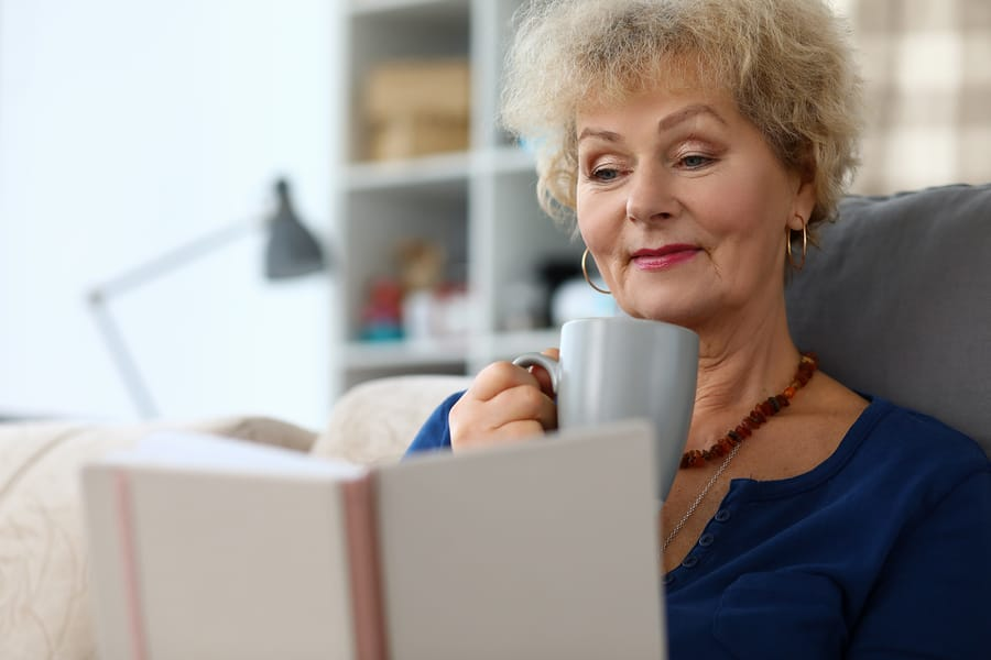 An older woman curled up on the couch reading a book and drinking tea.
